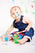 kleines junges baby malt mit Farben und pinsel