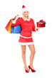 Female in christmas costume holding a gift and shopping bags