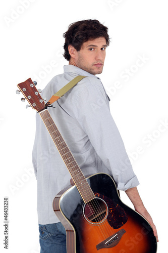 Man with acoustic guitar walking away from the camera