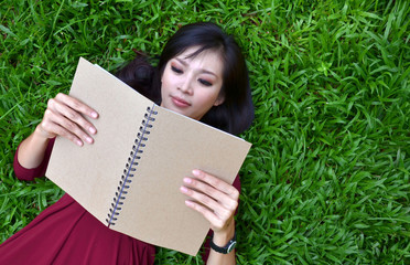 Woman lying on green grass with  book