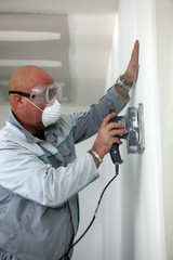 Man wearing mask and goggles whilst sanding wall