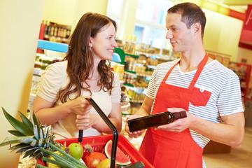 Mitarbeiter berät Kundin im Supermarkt