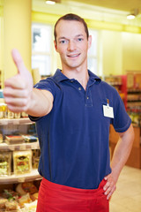 Verkäufer im Supermarkt hält Daumen hoch