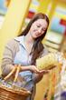 Frau betrachtet Nudelpackung im Supermarkt