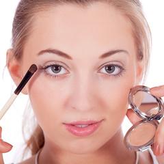 junge hübsche frau trägt makeup auf das Gesicht auf
