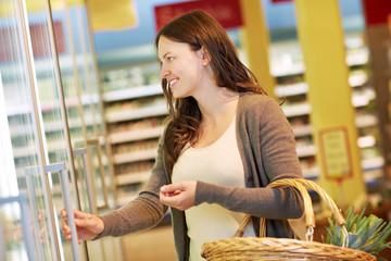 Frau öffnet Tiefkühltruhe im Supermarkt
