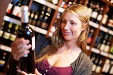 Frau liest Etikett einer Weinflasche