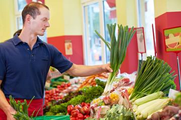 Supermarkt-Azubi füllt Gemüsestand auf