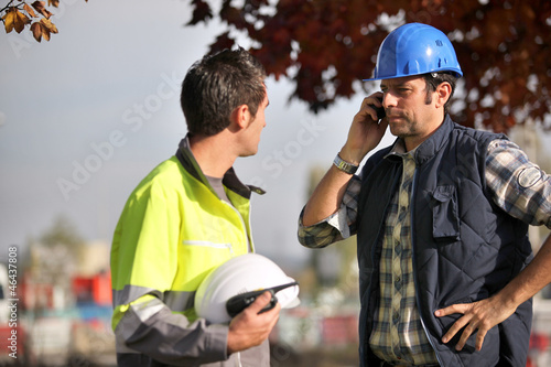 Construction workers on site with a phone