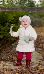 little girl with money in their hands in a forest