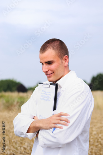 Young agricultural scientist in the wheat field smiling