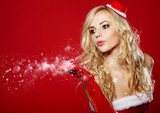 pretty young brunette woman dressed as Santa blowing on the snow