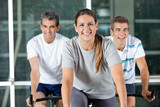 Men And Woman On Exercise Bikes