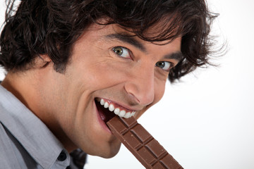 Man biting into chocolate bar