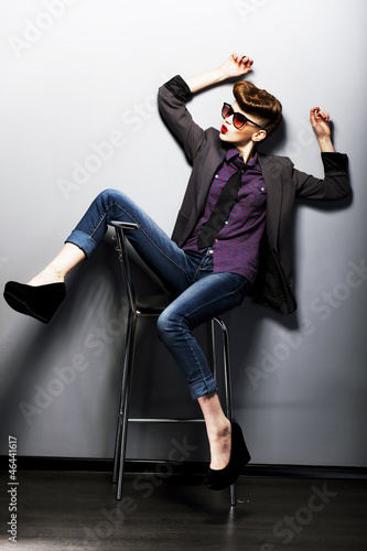Pin-up girl in sunglasses sitting. American retro style