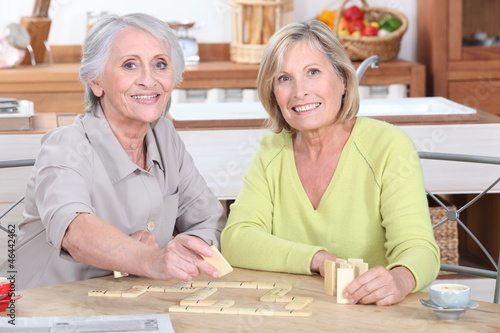 duo of retired ladies playing scrabble in the kitchen