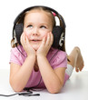 Cute little girl enjoying music using headphones