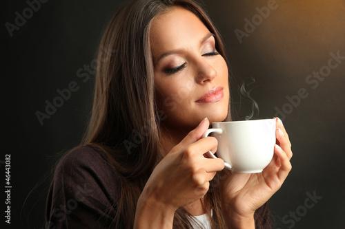 Naklejka Piękna młoda kobieta z filiżanką kawy na brązowym tle