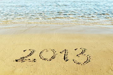 "The inscription ""2013"" on a beach sand"