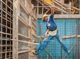 Construction worker balancing between scaffold and formwork fram poster