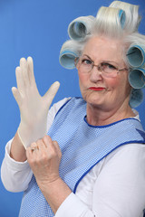 Granny with her hair in rollers putting on a latex glove