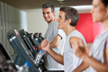Man Running On Treadmill In Fitness Club