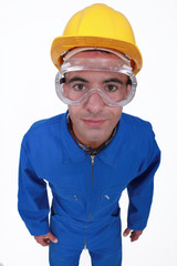 craftsman in overalls wearing protection glasses