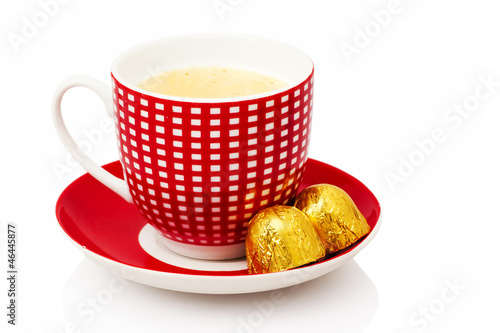 Cup of coffee with chocolate bonbons on white background