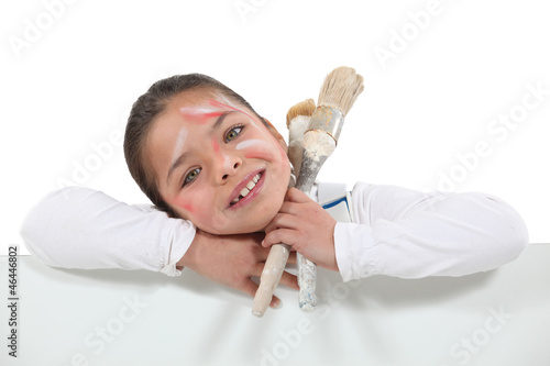 Messy little girl holding paint equipment