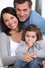 Smiling parents and their little girl
