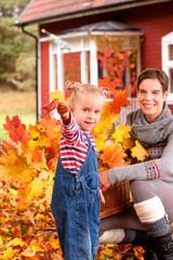 Mutter mit kleiner Tochter vor Haus in Schweden im Herbst