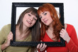 Women holding wooden frame