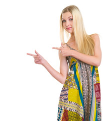 Girl in dress pointing on copy space