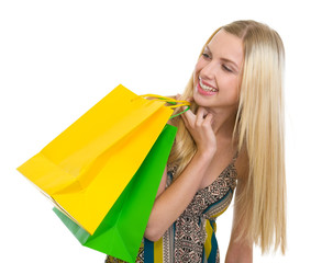 Smiling teenage girl with shopping bags looking on copy space