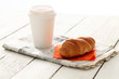 Still hot coffee with fresh croissant on newspaper over wooden s