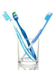 Toothbrushes in glass isolated on white