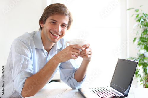 Young and handsome man drinking his coffee during a work break