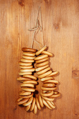 tasty bagels on rope, on wooden background