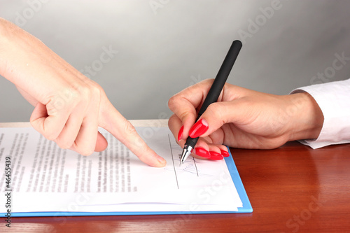 signing of  treaty on wooden table on color background