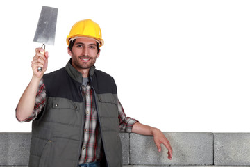 Builder with a bucket trowel and block wall