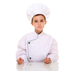 Little boy chef in uniform looking at camera