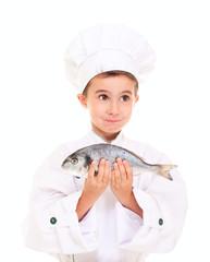 Little boy chef in uniform surprised holding dorado fish