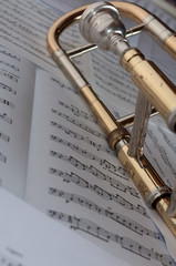A trombone resting on a background of music