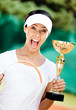 Young female tennis player won the cup at the sport competition