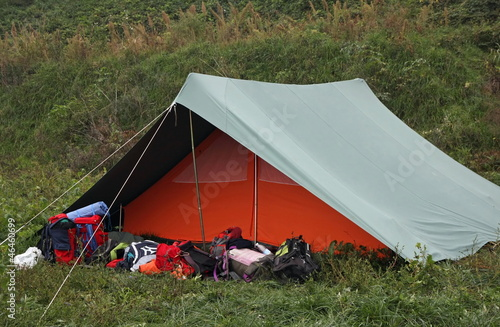 orange and green tent with many backpacks