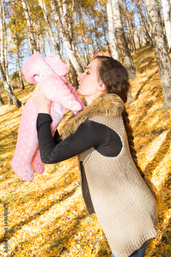 Happy young mother playing with little daughter in autumn park