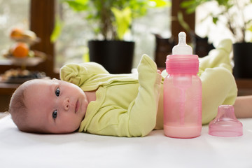 Newborn baby girl with a bottle of milk.
