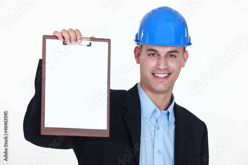 businessman wearing helmet and holding a notepad