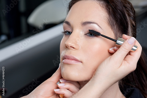 Make up artist applying mascara to a fashion model/bride