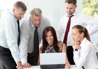 Beautiful female executive pointing at laptop screen